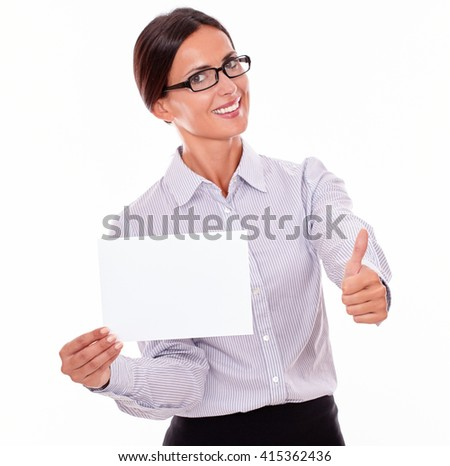 Indifferent brunette businesswoman with glasses, wearing her long hair tied back, and a button down shirt, holding a blank copy space in one hand, gesturing thumbs up with the other hand