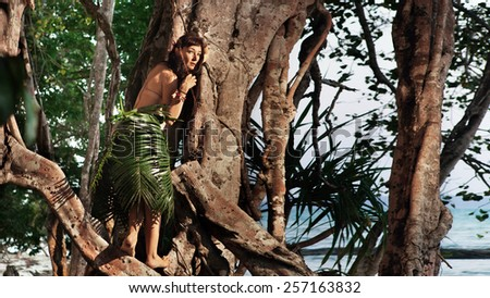 Indigene woman in the palm skirt on the tropical forest and sea background - stock photo