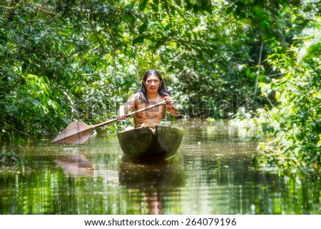 INDIGENOUS ADULT MAN ON TYPICAL WOODEN CANOE CHOPPED FROM A SINGLE TREE NAVIGATING MURKY WATERS OF ECUADORIAN AMAZONIAN PRIMARY JUNGLE