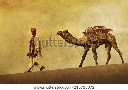 Indigenous Indian man walking through the desert with his camel. - stock photo