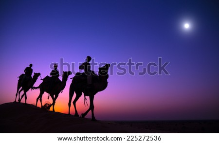 Indigenous Indian men riding through the desert with their camel. - stock photo