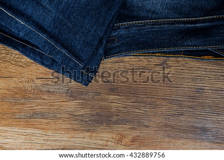 Indigo Faded Heavy Worn Denim / Jeans in Wooden Background - stock photo
