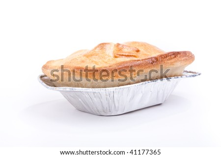Individual short crust pastry steak pie in silver foil tray isolated against white background