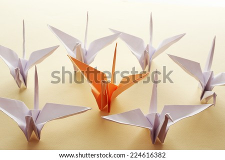 Individuality concept. Origami birds on light background - stock photo
