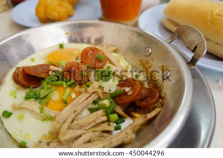 Indochina pan-fried egg with toppings in Thai style or Indochina Omelette. Breakfast is eaten in the northeast of Thailand. - stock photo