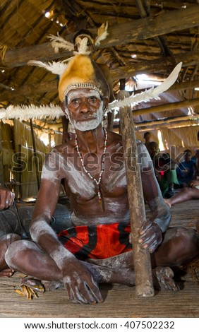 INDONESIA, IRIAN JAYA, ASMAT PROVINCE, JOW VILLAGE - JANUARY 19: Warrior Asmat tribe is sitting at home in traditional headdress and war paint. On January 19, 2012  Jow Village, Asmat province.