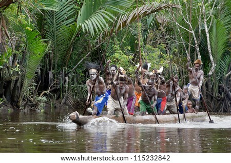INDONESIA, IRIAN JAYA, ASMAT PROVINCE, JOW VILLAGE - JUNE 28:  Asmat men paddling in their dugout canoe. Canoe war ceremony of Asmat people. New Guinea Island, Indonesia. June 28 2012 - stock photo