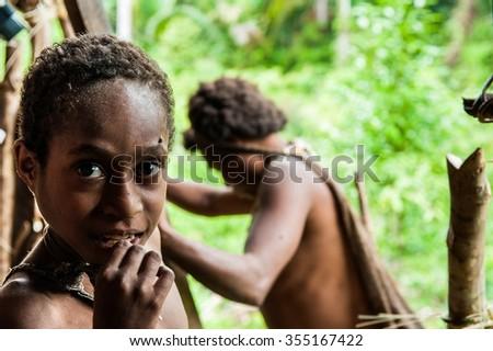 INDONESIA, NEW GUINEA, IRIAN JAYA, ONNI VILLAGE - JUNE 24: Portrait of Korowai girl in the traditional wooden house built on a tree. New Guinea Island, Indonesia. June 24 2012  - stock photo