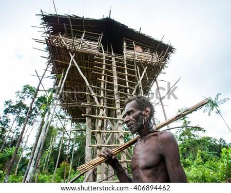 INDONESIA, ONNI VILLAGE, NEW GUINEA - JUNE 24: The Portrait Korowai man hunter with arrow and bow. Tribe of Korowai (Kombai , Kolufo).On June 24, 2012 in Onni Village, New Guinea, Indonesia - stock photo