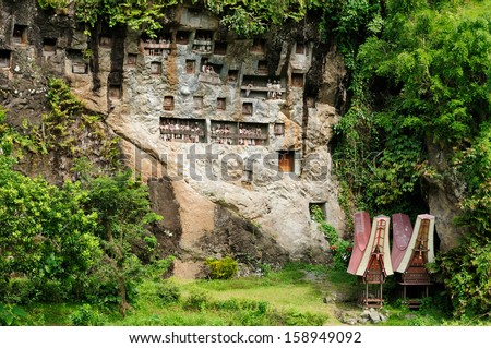 Indonesia, Tana Toraja - Londa, is a very extensive burial cave at the base of a massive cliff face.The entrance to the cave is guarded by a balcony of tau tau. - stock photo