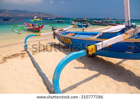 Indonesian boats on the tropical sand beach - stock photo