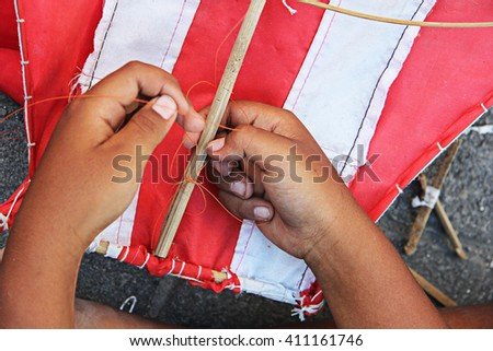Indonesian boy build (hands tie  stick and kite together with the string) a white and red kite, Kuta, Bali, Indonesia - stock photo