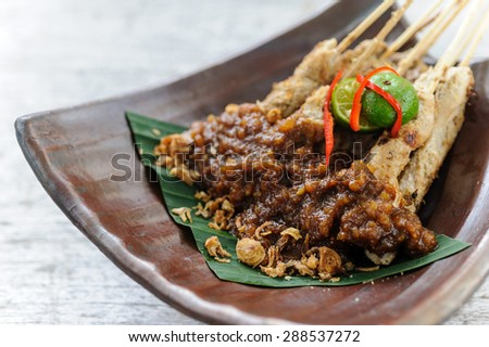 Indonesian chicken sate served with peanut sauce. - stock photo