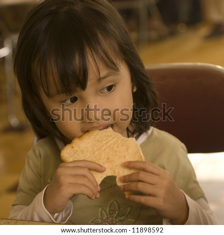 Indonesian girl eating shrimp cracker - stock photo