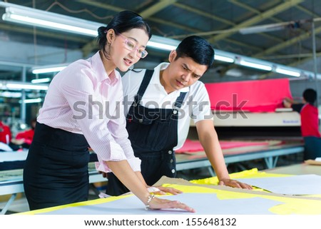 Indonesian Worker or foreman and dressmaker, tailor or designer looking at pattern on a table in a Asian textile factory - stock photo
