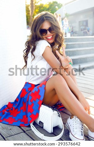 Indoor bright fashion summer portrait of stylish cheeky hipster woman,showing her tongue,have long brunette hairs perfect tanned fit slim body,wearing sneakers summer dress and trendy sunglasses.cool - stock photo