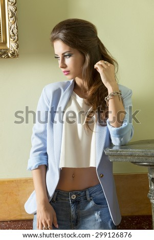 indoor fashion shoot of pretty brunette girl with casual modern cloche and long wavy hair. Wearing racket and jeans  - stock photo