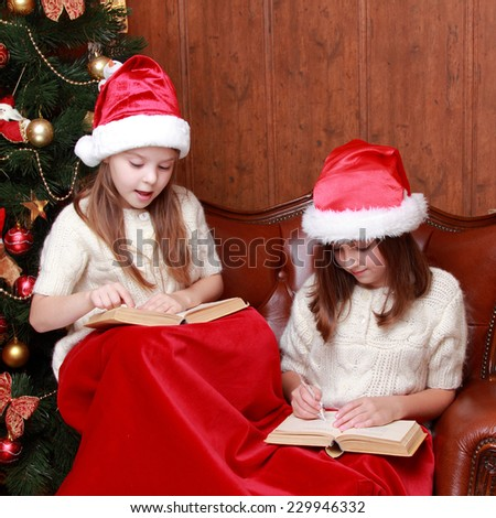 Indoor image of cheerful young girls at Christmas time on holiday theme/Beautiful little girls holding books - stock photo