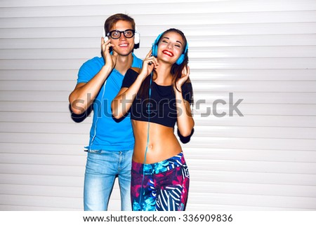 Indoor night portrait of crazy sexy hipster couple having fun and making own party, bright sportive clothes ,listening music at headphones. - stock photo