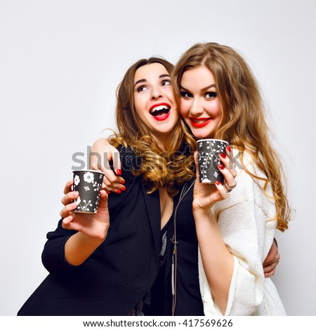 Indoor party portrait of couple best friends, blonde and brunette pretty girls having fun and drinking cocktails, black and white party, celebration, white wall, flash, glamour elegant clothes, happy  - stock photo