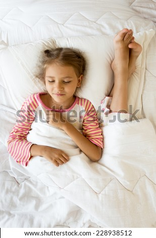 Indoor photo of girl lying next to sisters feet on pillow