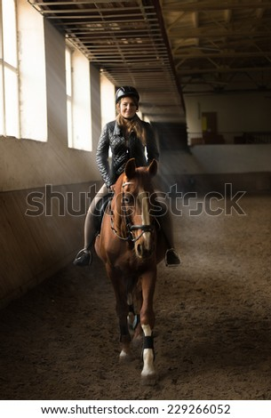 Indoor photo of young woman jockey riding horse on manege - stock photo