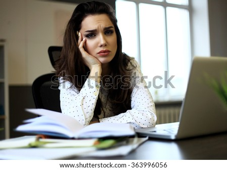 indoor picture of bored and tired woman taking notes