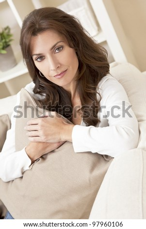 Indoor portrait of a beautiful young brunette woman in her thirties or forties holding a cushion and looking thoughtful - stock photo