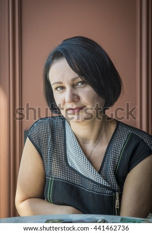 Indoor Portrait of a mature woman in a fashionable dress. - stock photo