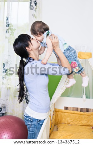 indoor portrait of a young woman with a toddler in the nursery