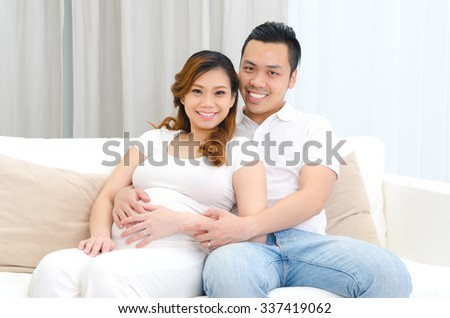 Indoor portrait of beautiful asian pregnant woman and her husband - stock photo