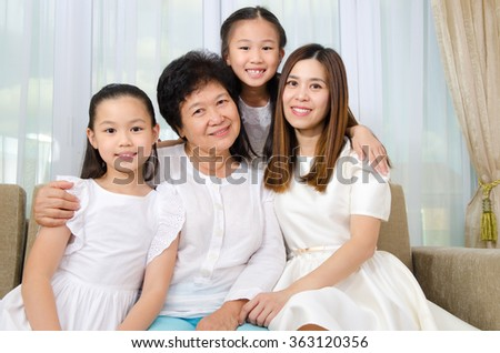 Indoor portrait of cheerful asian senior woman together with daughter and grandchildren - stock photo
