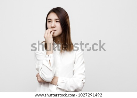 Indoor portrait of young attractive tricky woman thinking, getting nervous and biting her nails. Negative stressed facial expressions, emotions and feelings concept