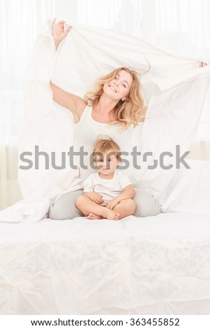 indoor portrait of young beautiful woman enjoying her morning time at home with her baby - stock photo