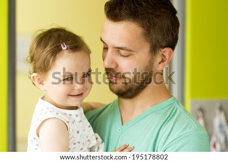 Indoor portrait of young father hugging his little daughter - stock photo