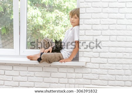 indoor portrait of young happy smiing child boy with little black cat sitting near window at home - stock photo