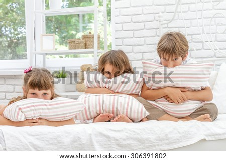 indoor portrait of young happy smiing children, girls and boy, in bed, happy morning time - stock photo