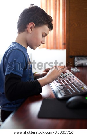Indoor shot of a boy typing on a keyboard - stock photo