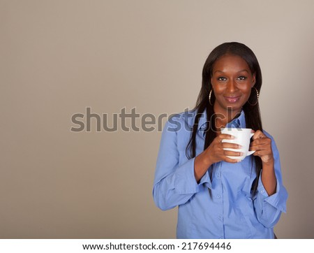Indoor shot of a pretty African American woman in a blue blouse enjoying a cup of coffee or tea with room for copy - stock photo