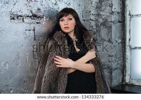 Indoor shot of young fashionable woman wearing fur coat - stock photo