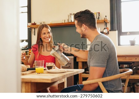 Indoor shot of young man serving coffee to his girlfriend having breakfast in kitchen at home. Smiling young couple having breakfast and looking at each other. - stock photo