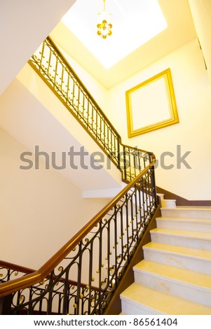 Indoor spiral staircase, the yellow light - stock photo