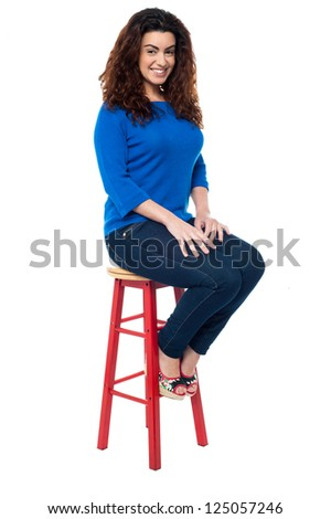 Indoor studio shot of a stylish female seated on red stool. - stock photo