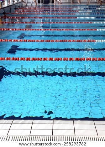 indoor swimming pool pool with blue water and the swimming lanes - stock photo