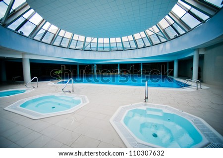 Indoor swimming pool with jacuzzi on resort - stock photo