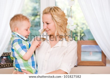 Indoors portrait of a very happy mom and son together. - stock photo