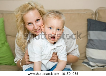 Indoors portrait of young child with his fashionable young mother. - stock photo