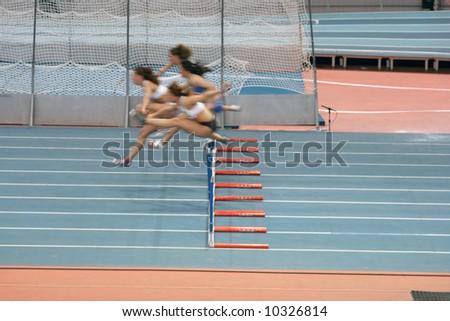 indoors women 60 meters low hurdlers race in action - stock photo