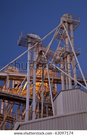 industrial abstract - top of a grain elevator with gravity flow pipes at night - stock photo