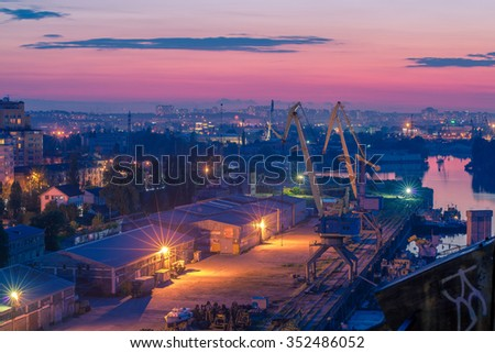 Industrial area with river port at purple sunset - stock photo